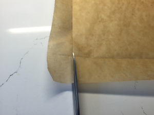 using a scissor, make one cut at each of the four corners. This will create a small flap.