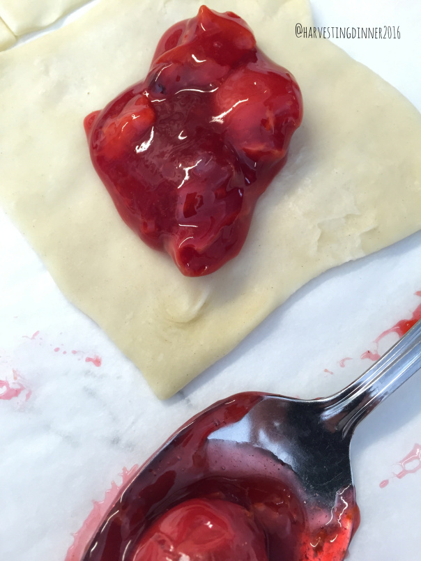 Puff pastry squares getting a big scoop of cherry pie filling